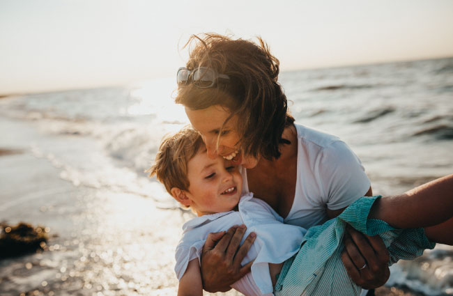 mother and son on beach protected by life insurance